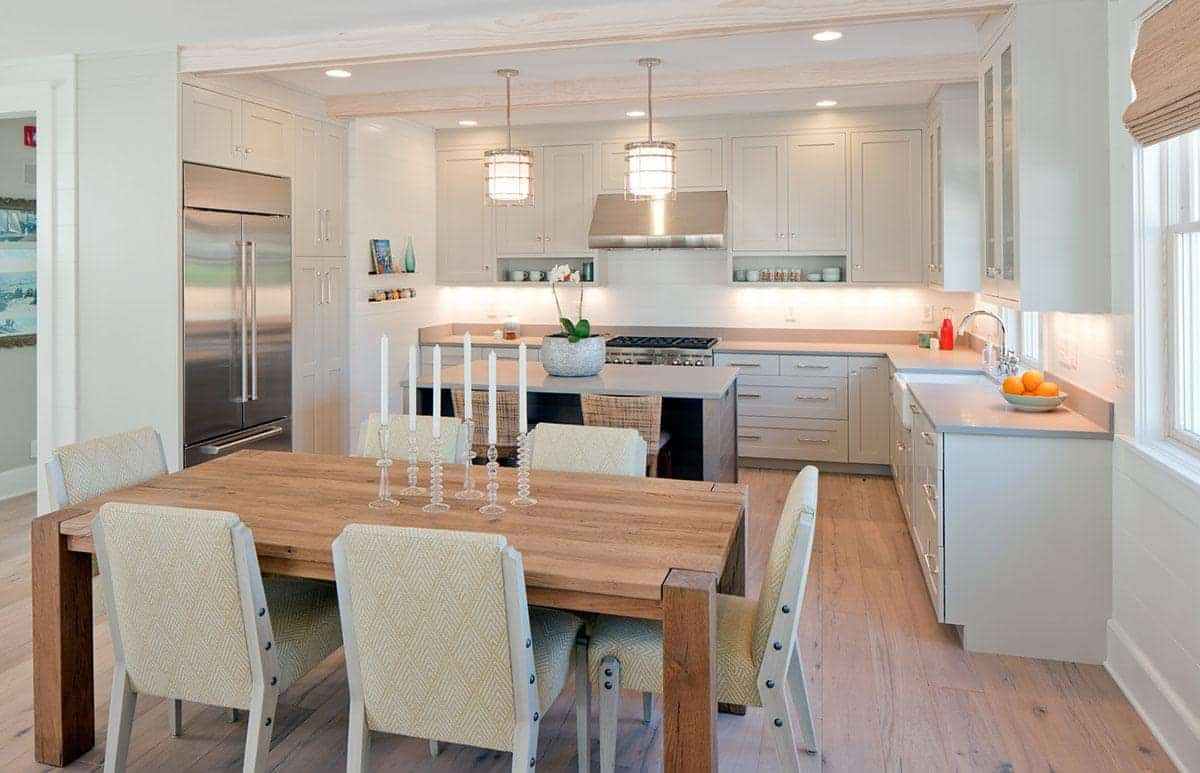 This kitchen is beside the dining area that has a wooden table matching the hardwood flooring. This is complemented by the light gray L-shaped peninsula and the kitchen island with gray countertops illuminated by two pendant lights.