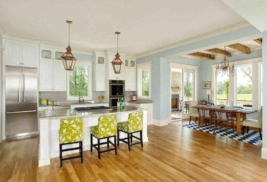 This Beach-style kitchen has charming green floral cushioned stools that stand out against the white and gray hues that mostly dominate the peninsula and island. This is complemented by a couple of pendant lights that match the hardwood flooring.