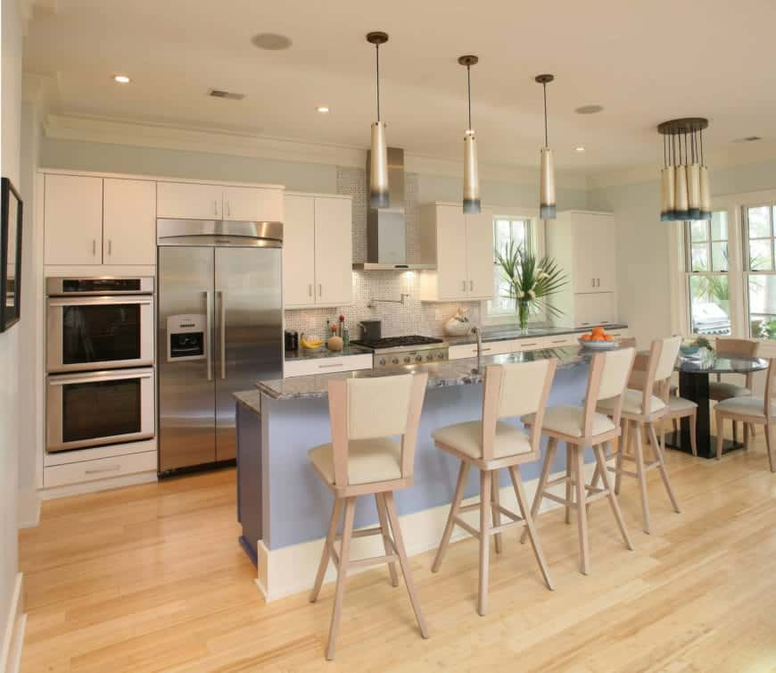 The cheerful pastel blue hue of the kitchen island complements the light hardwood flooring. This kitchen island has a second tier of black marble countertop for a bar that has beige stools topped with stylish pendant lights.