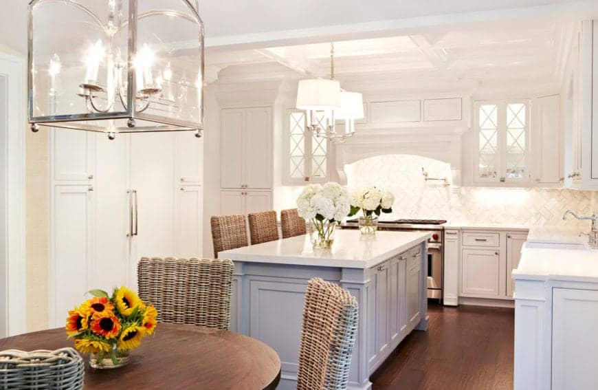 The white tray ceiling is further brightened by the white lights of the pendant lights hanging over the white countertops of the kitchen island same as the peninsula that has off-white backsplash tiles illuminated by lights under the floating cabinets.