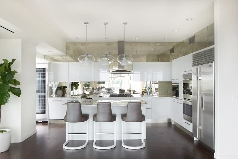 The white L-shaped peninsula with modern cabinetry is paired with sleek gray tiles on the backsplash that extends to the upper walls above the floating cabinets. These are so sleek that they are like mirrors reflecting the rest of the kitchen.