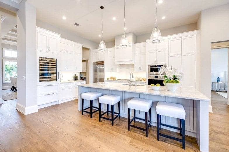 This is a predominantly white kitchen with a white ceiling that has recessed lights brightening the white cabinets and drawers of the peninsula augmented by lovely pendant lights hanging over the large kitchen island paired with white cushioned stools.