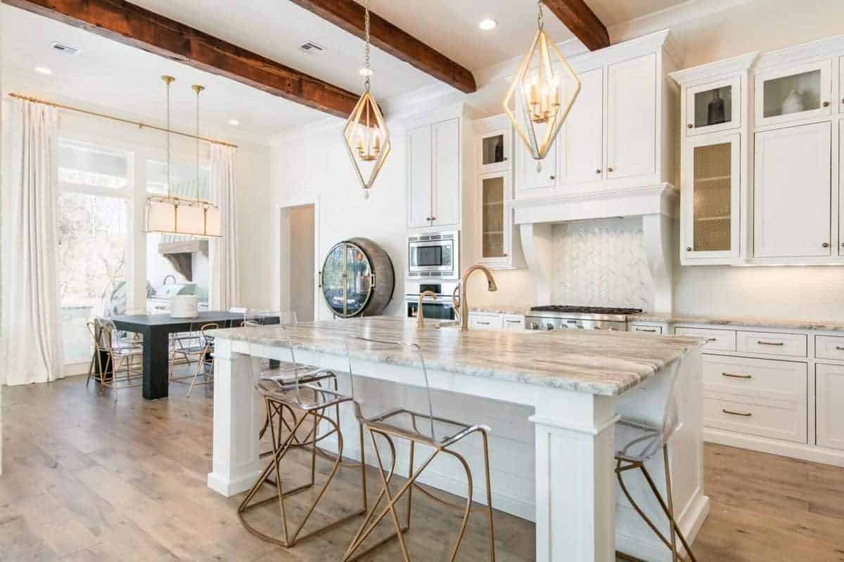The white ceiling with exposed wooden beams that match the hardwood flooring are a nice background for the white wooden structures of the kitchen. These are accented with brass elements on the cabinetry handles, faucet and legs of the modern stools as well as the pendant lights.
