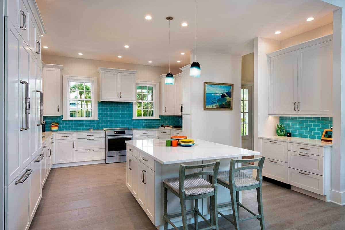 The green tiles of the backsplash stands out against the white cabinetry of this Beach-style kitchen with hardwood flooring that complements the white ceiling and walls adorned with a framed artwork.