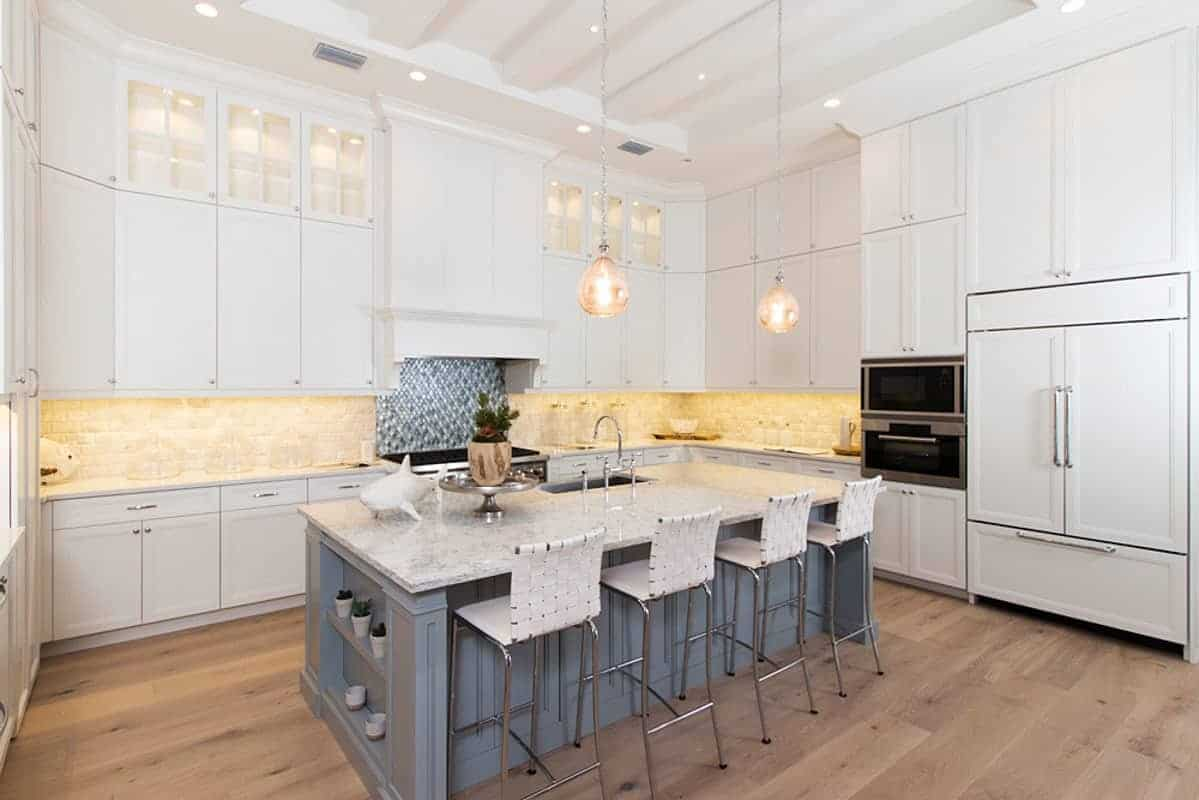 The highlight of this Beach-style kitchen is the gray kitchen island that complements the hardwood flooring and the white U-shaped peninsula that houses the modern appliances accented by a beige stone backsplash illuminated with warm light.