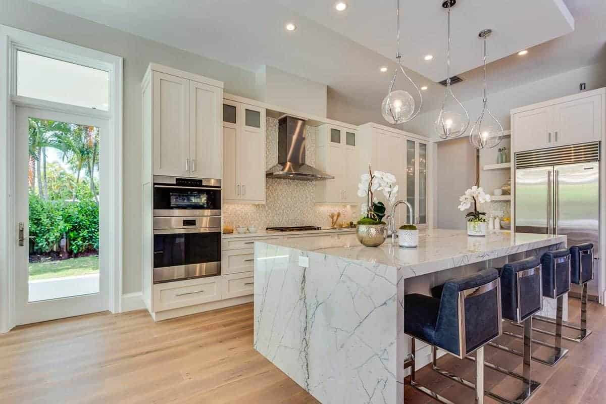 In the middle of the hardwood flooring of this kitchen is the white marble waterfall kitchen island paired with modern stools that has green leather cushions and stainless metal legs matching the modern appliances of the white peninsula.