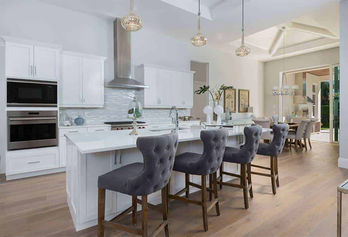 The hardwood flooring is complemented by the dark wooden legs of the gray cushioned stools of the kitchen island that has the same white shaker cabinets and drawers as the peninsula complemented by a gray patterned backsplash.