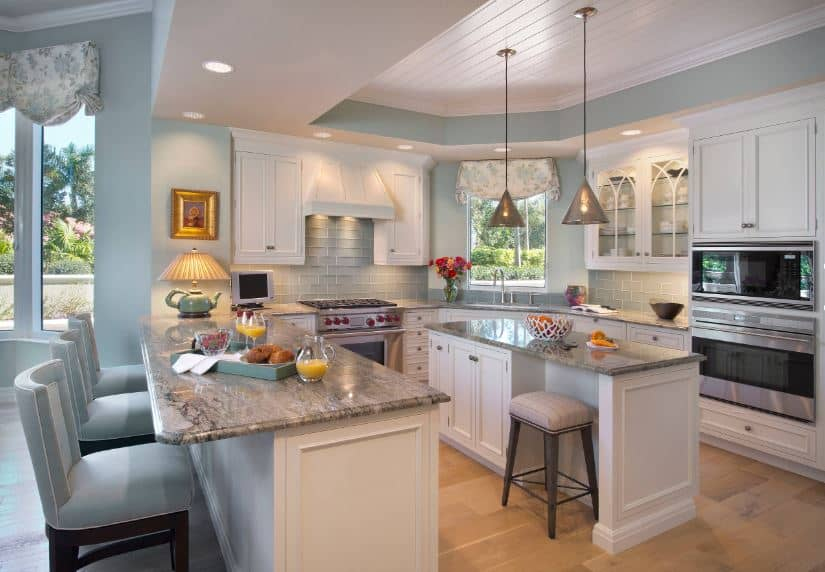 The beautiful tray ceiling has a white middle tray framed with delightful pastel green hues that extend to the walls and the backsplash tiles of the white U-shaped peninsula encircling the small kitchen island topped with pendant lights.