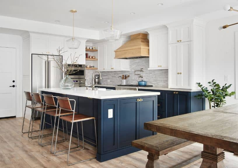 The brilliant navy blue wooden kitchen island matches with the peninsula. These are contrasted by the white countertops and the white wall-mounted cabinets above the peninsula that flanks the wooden vent hood.