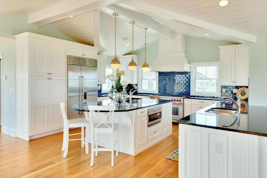 The irregular arches of the white ceiling are complemented by a wooden shiplap finish with exposed wooden beams supporting three elegant pendant lights hanging over the black countertop of the kitchen island that matches with the large U-shaped peninsula.