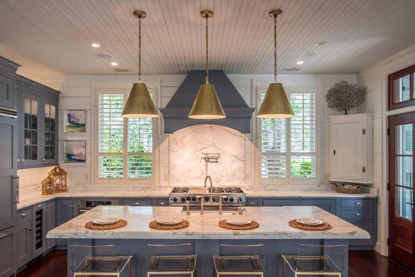 The three large pendant lights matches with the brass frame of the modern stools paired with the gray kitchen island that has a white marble countertop. This is mirrored by the L-shaped kitchen peninsula and its gray vent hood.