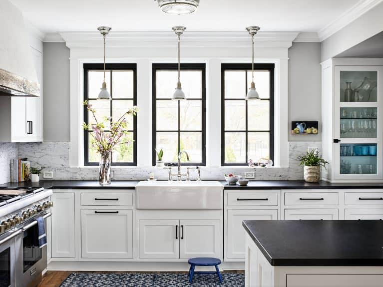 The white shaker cabinets and drawers of this Beach-style kitchen are further brightened by the natural lights coming in from the three windows above the sink area that has a large porcelain rectangular basin sink topped with three small pendant lights.
