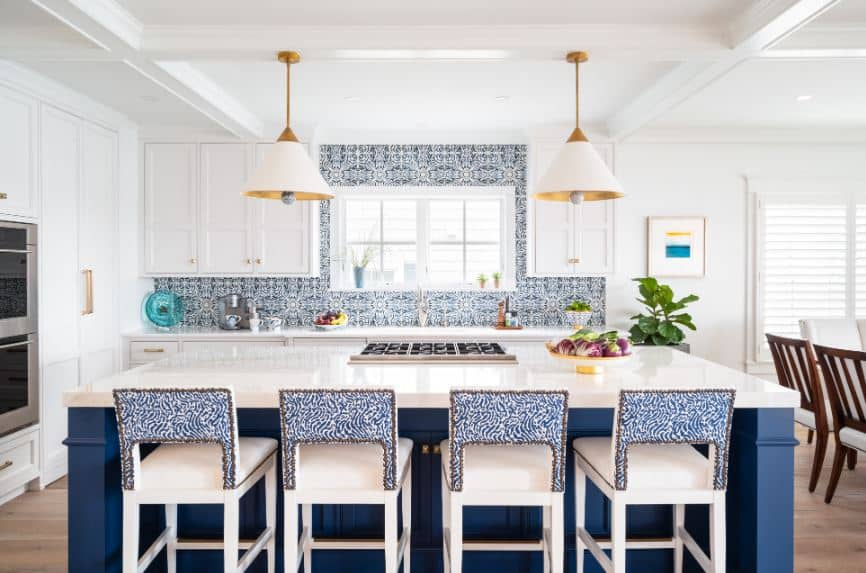 The white stools paired with the blue kitchen island has charming patterned blue backs that match the blue patterns of the backsplash tiles of the white peninsula that matches with the white coffered ceiling.