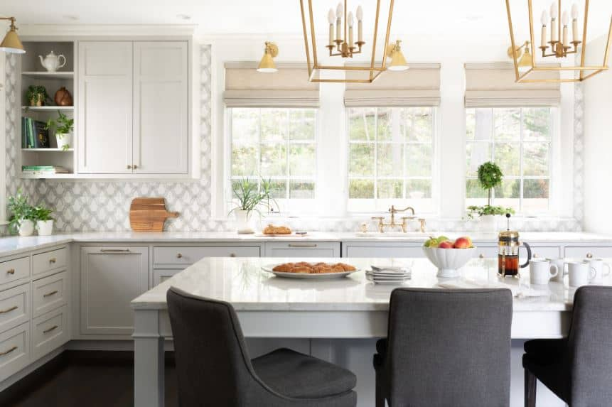 This bright and airy Beach-style kitchen has an elegant gray and white patterned wallpaper that also serves as a backsplash and complement to the white countertop of the L-shaped peninsula with light gray cabinets and drawers.