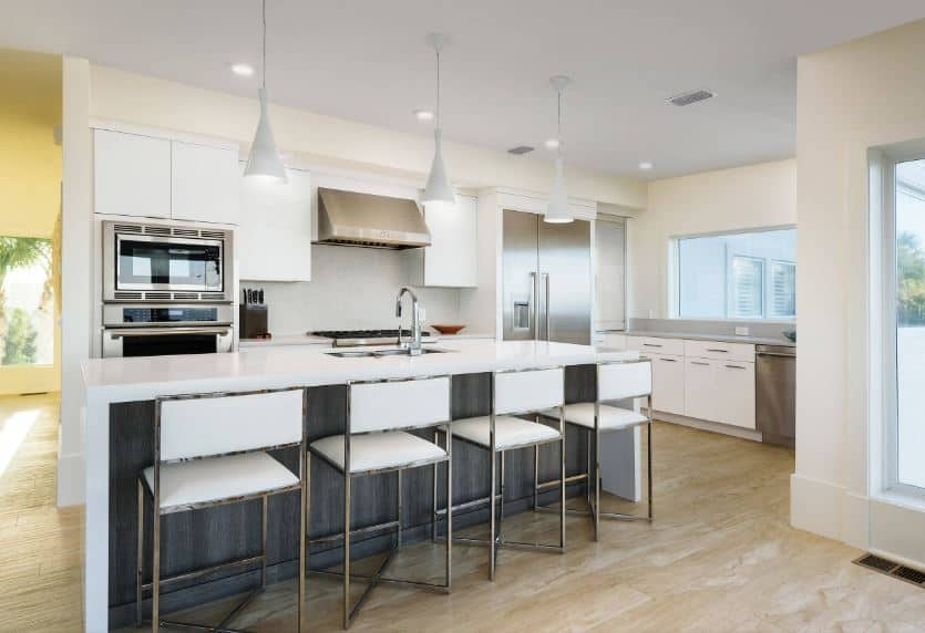 This wonderful kitchen is a nice fusion of modern elements and Beach-style elements. It has modern white cabinetry on its peninsula that pairs well with the white waterfall kitchen island paired with modern white stools.