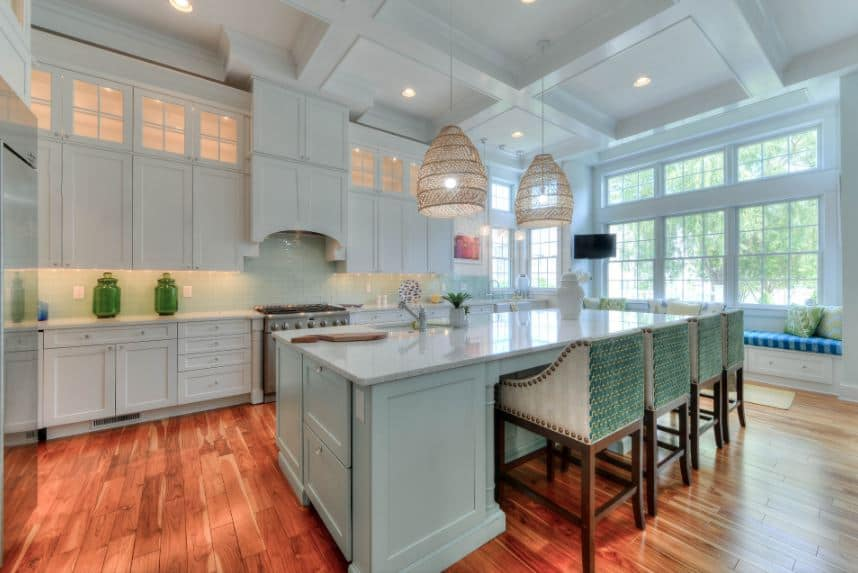 This Beach-style kitchen is dominated by the cheerful light green hue on the high coffered ceiling, large windows, kitchen island and the cabinets of the kitchen peninsula housing the stainless steel stove-top oven.