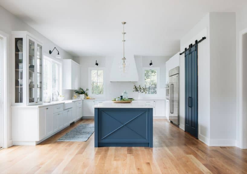 The stand out element of this Beach-style kitchen is the navy blue kitchen island with a white countertop that matches the large L-shaped peninsula. This navy blue hue is also seen on the wooden sliding door beside the stainless steel fridge embedded into the white wall.