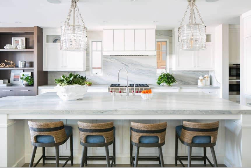 The white marble countertop of the white kitchen island is paired with a couple of cylindrical glass pendant lights with silver chains that match the faucet and the stainless steel stove-top oven flanked by the white peninsula.