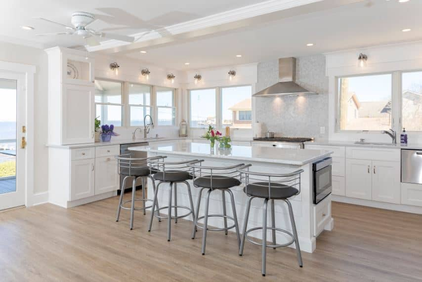 This predominantly white Beach-style kitchen has white wooden structures that serve as a charming background for the stainless steel and gray elements of the stools and stainless steel appliances illuminated by the row of windows surrounding the kitchen.