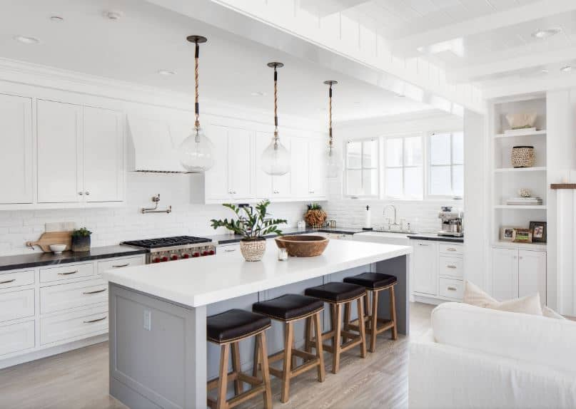 This brilliant kitchen has a white tray ceiling, white stone textured walls and white cabinetry of the L-shaped peninsula. This is contrasted by the black countertop of the peninsula that is complemented by a gray hardwood flooring.