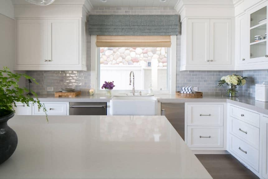 The gray backsplash tiles of this bright kitchen are arranged in a brick wall pattern for that homey quality that warms up the white shaker cabinets and drawers of the peninsula that houses the stainless steel appliances.