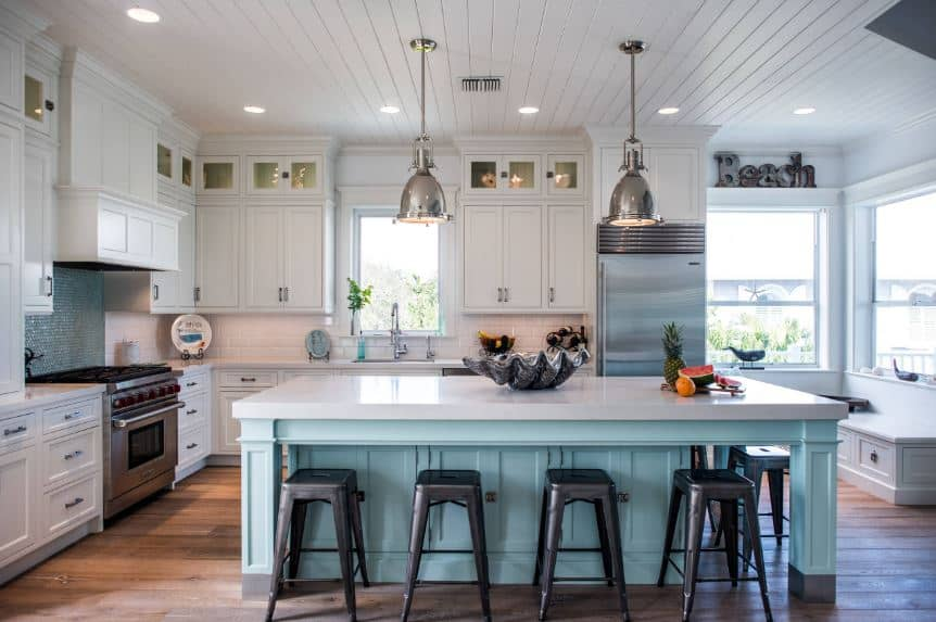 The charming light green wooden kitchen island stands out against the dark hardwood flooring. This cheerful light green hue is also applied on the backsplash tiles of the cooking area that has a white vent hood blending with the peninsula.