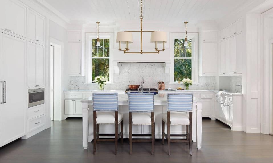 This Beach-style kitchen has a nice contrast between the dark hardwood flooring the white shaker cabinets and drawers of the peninsula that blends with the white shiplap ceiling bearing an elegant brass pendant light over the kitchen island.