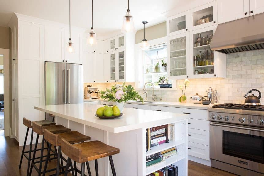 The white wooden kitchen island that has bookshelves on the side and a white countertop that matches the peninsula is paired with three stools with wooden seats that matches with the hardwood flooring.