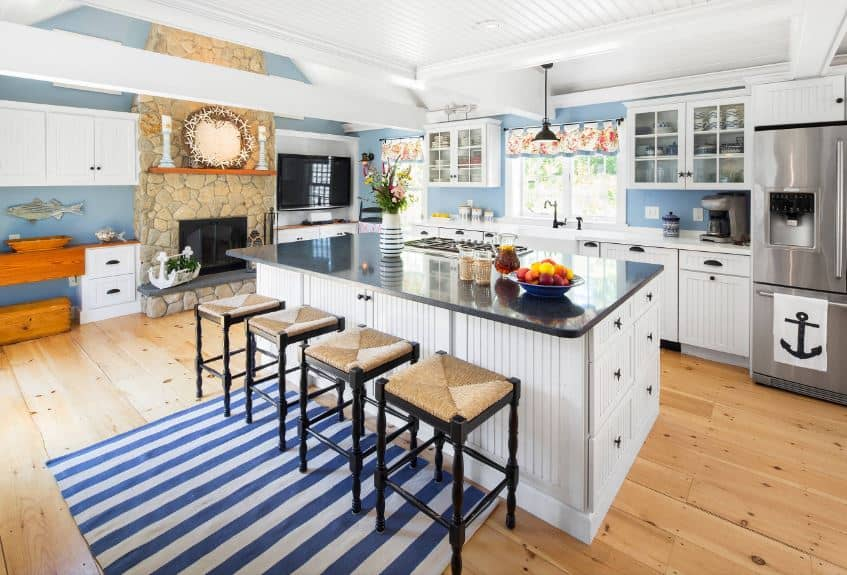 This large Beach-style kitchen has light hardwood flooring that pairs with the stone inlay of the fireplace on the far wall. This is accented with blue walls that brightens the white cabinetry of the kitchen island and peninsula with a striped finish to them.