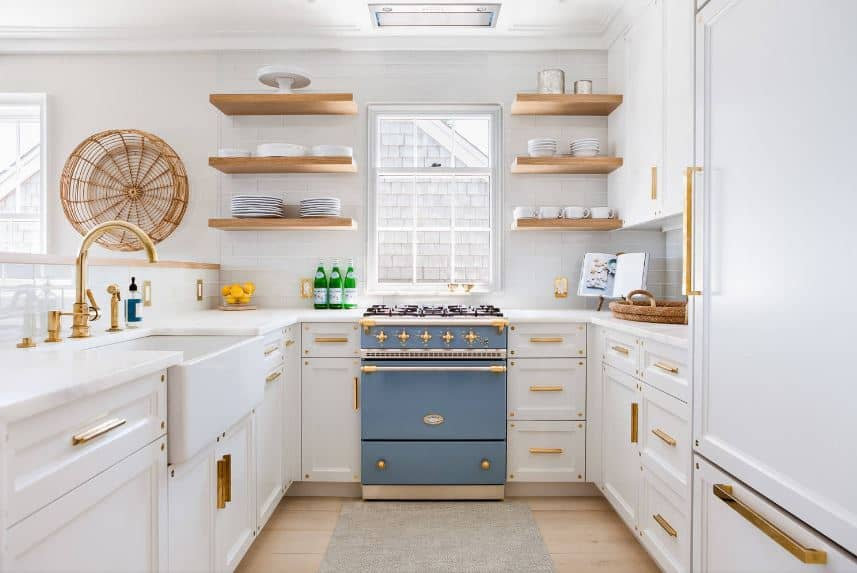 This beautiful white Beach-style kitchen has white cabinets and drawers accented by the golden fixtures and handles that go well with the bare wooden shelves and woven basket mounted on the white wall to serve as artwork.