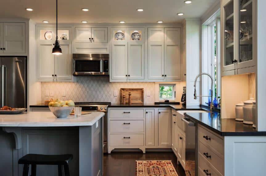 The light gray shaker cabinets and drawers of this lovely kitchen is paired with a patterned wallpaper for that elegant accent that goes well with the black countertop matching the dark hardwood flooring topped with a patterned area rug.