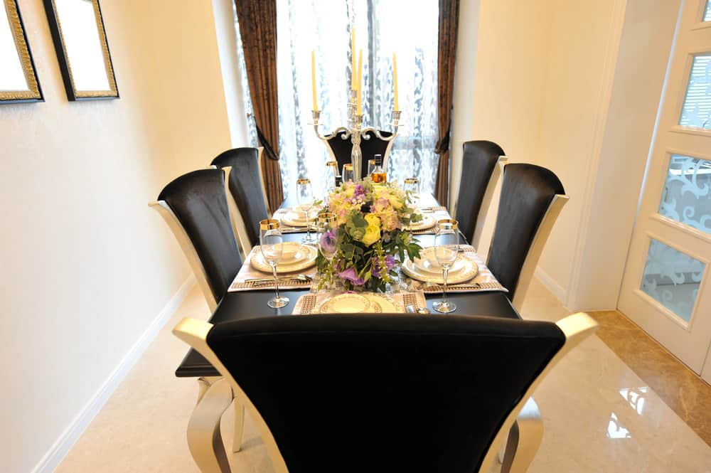 A gorgeous dining room featuring beige walls with a black accent. The dining table and chairs set looks absolutely luxurious.