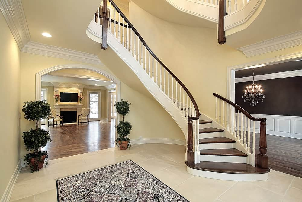 This spacious foyer has beige walls and a beige ceiling that matches the beige tiles of the flooring that is topped with an intricate-patterned area rug for contrast. This foyer leads to the living room through an arched entryway flanked with potted plants that go nicely with the beige walls.