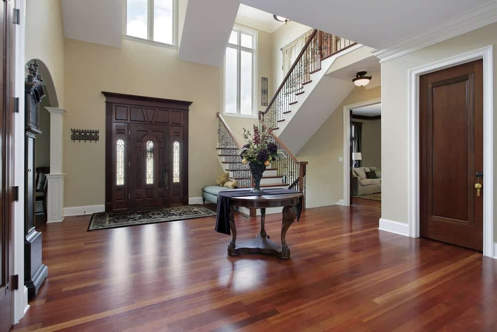 The hardwood flooring is a perfect match for the wooden door and its wooden fitting with an elegant finish. This wooden door contrasts with the beige walls and the high white ceiling with windows to fill the vertical space. There is a wooden circular table in the middle of the floor that displays a lovely flower vase.