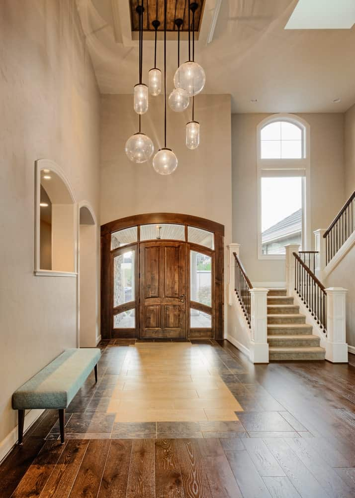 The large wooden main door is framed with natural light coming in from the sidelights and the arched transom windows above. This presents a nice contrast with the beige walls making way for the arched entryways that match the arched windows.