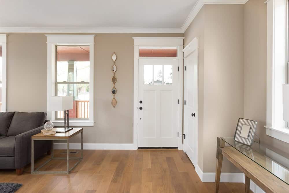 This is a small and simple foyer that seamlessly transitions to the living room area with the same white ceiling, beige walls and hardwood flooring. The white wooden door has a built-in window matched with a small horizontal transom window above.