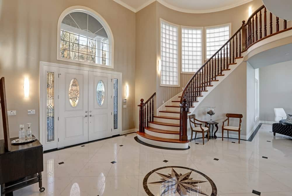 The elegant white double doors have built-in oblong windows with intricate iron fittings that match with the fittings of the sidelights. The transom window is a gigantic arched glass structure that complements the high beige walls and white ceiling.