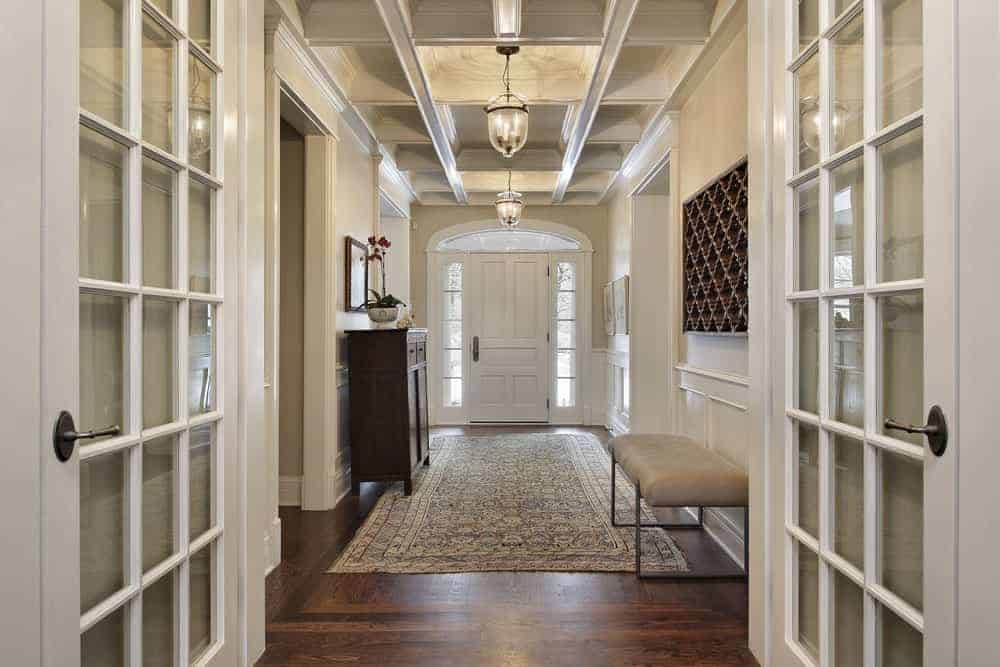 White french door opens to this foyer with hardwood flooring topped by a vintage rug and coffered ceiling with hanging glass pendant lights.