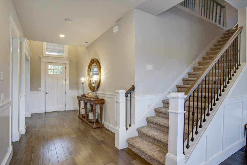 Beige foyer showcases a straight staircase covered with velvet carpet. It includes a wooden console table and round mirror mounted above the white wainscoting.