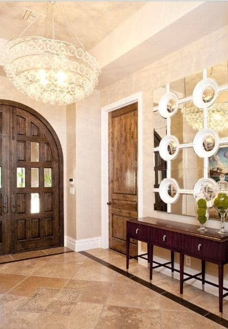 A huge glass pendant illuminates this foyer boasting an arched entry door and a wooden console table that's paired with a stylish mirror.