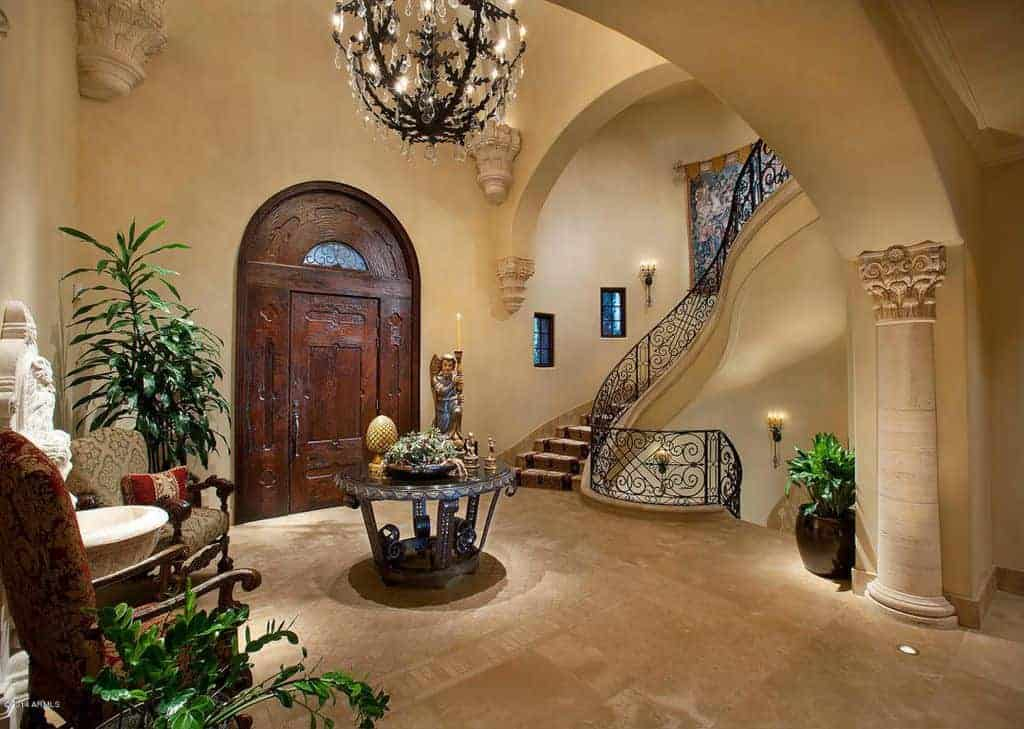 Tropical foyer showcases an arched front door and round center table that's accompanied by cushioned armchairs lighted by an oversized pendant light.