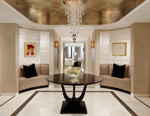 Contemporary foyer with seat nooks and a round dark wood center table in the middle topped with a decorative bowl and illuminated by a cascading crystal chandelier.
