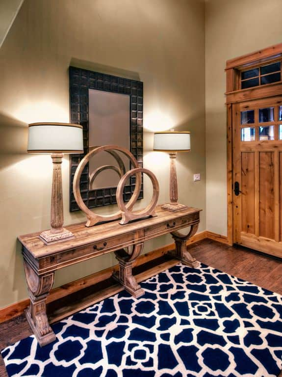 A pair of wooden round decors and table lamps sit at a natural wood console table in this foyer with a black mirror and deep blue rug that lays on wood plank flooring.