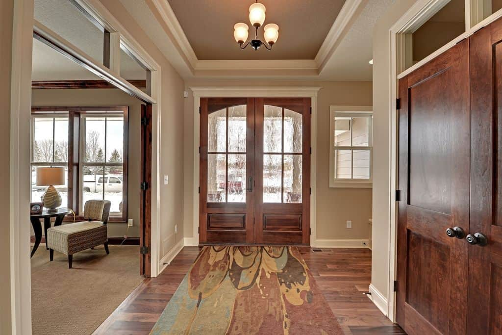 Craftsman foyer features a wooden french door that complements with the hardwood flooring topped by a printed rug. It is lighted by a chandelier that hung from the tray ceiling.
