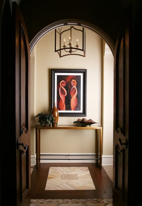 A dark wood arched door opens to this beige foyer showcasing an interesting wall art and a wooden console table illuminated by a caged pendant.