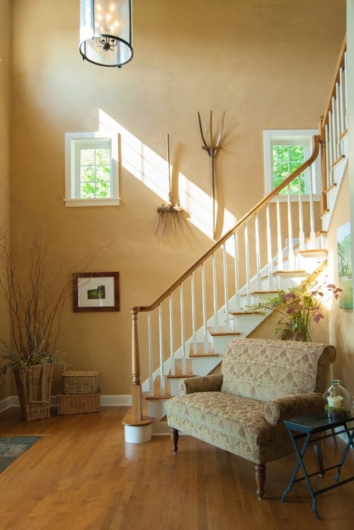 Farmhouse foyer offers a tufted seating paired with a black side table. It is designed with a twig plant and wooden wall arts that hung above the staircase.