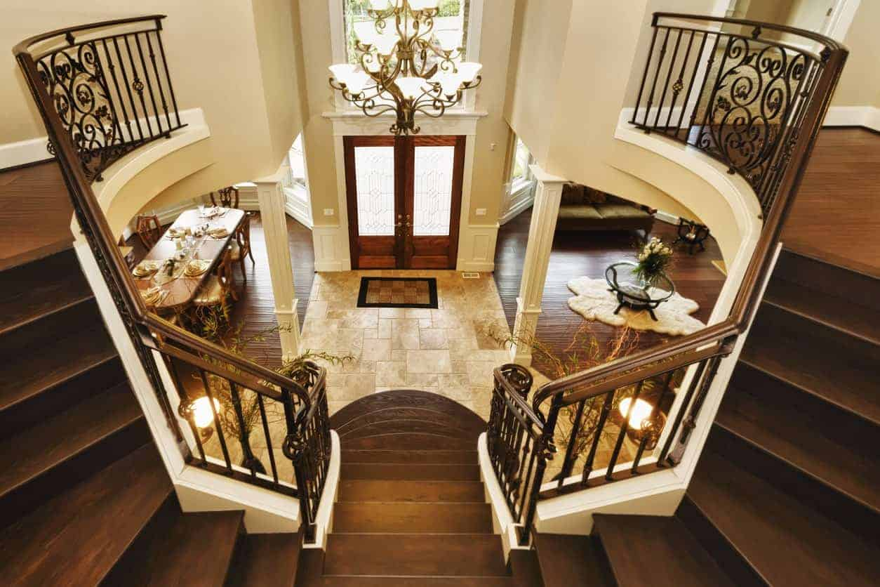 Beige foyer illuminated by a fancy chandelier that hung over the wooden bifurcated staircase lined with white columns and faces the entry double door.