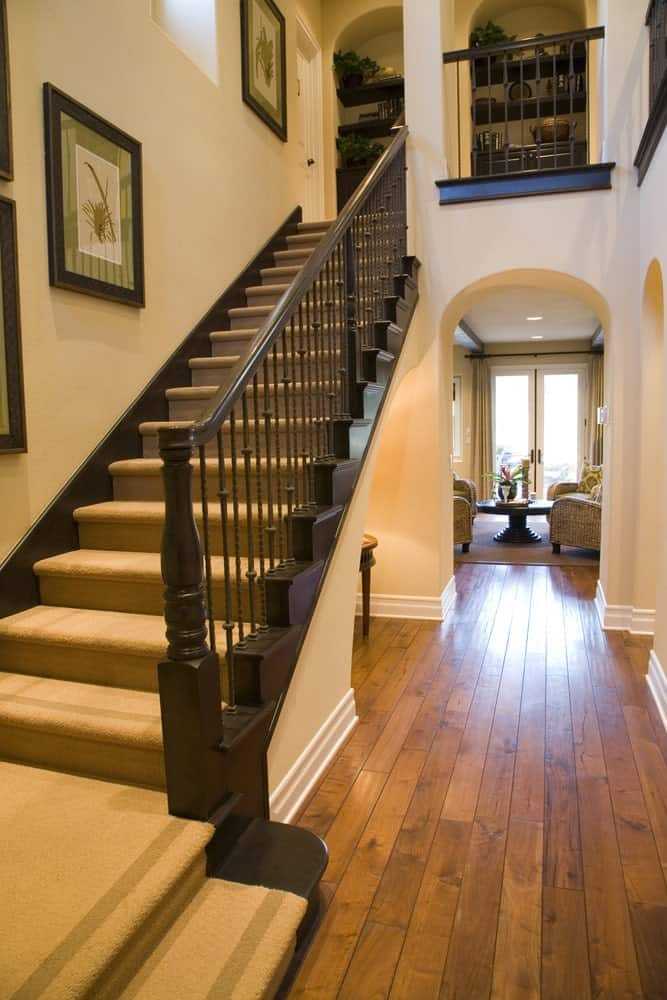 Narrow foyer showcases open archways and a wooden staircase covered with beige carpet and accented with green framed wall arts.