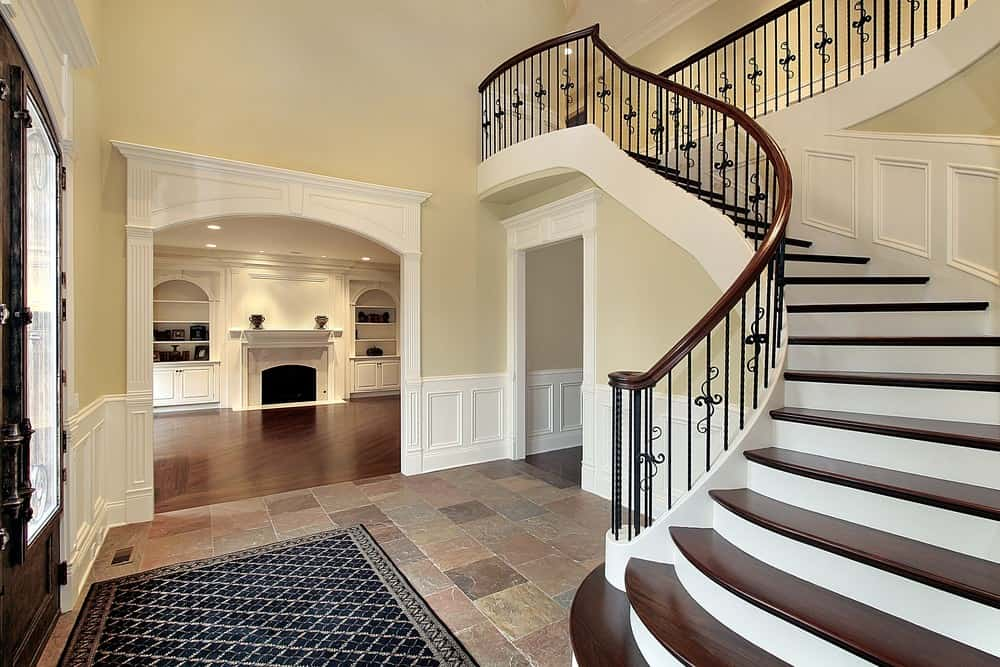 This foyer showcases a concrete tiled flooring topped with a patterned rug and curved staircase fixed to the beige wall with white wainscoting.