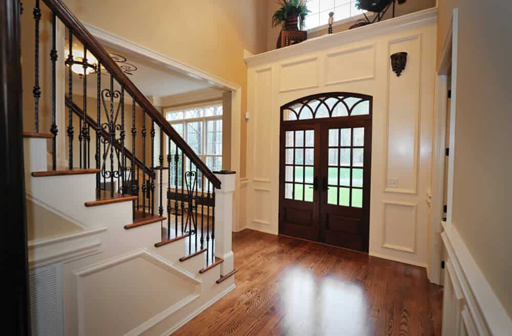 This foyer features a wooden entry door fitted to the white wainscoting. It has hardwood flooring and straight staircase framed with ornate wrought iron balustrade.